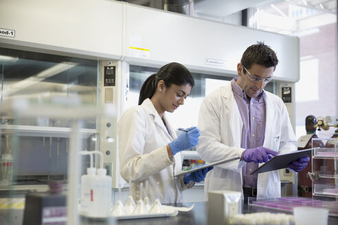 Scientists with digital tablet and clipboard working together in laboratory - HEROF30978