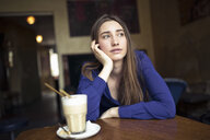 Young woman sitting at table in a cafe looking sideways - PNEF01317