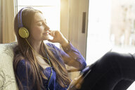 Relaxed young woman sitting on a chair wearing headphones - PNEF01320