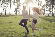 Happy young couple running hand in hand on meadow - PNEF01323