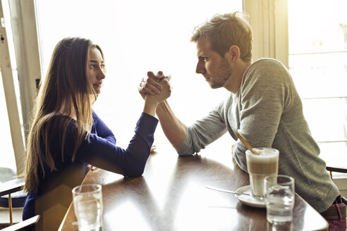 Young couple in a cafe arm wrestling - PNEF01326