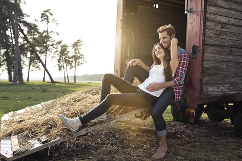 Happy young couple sitting on trailer in the countryside - PNEF01332