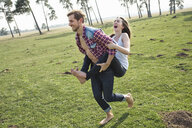 Happy young man carrying girlfriend piggyback on meadow - PNEF01335