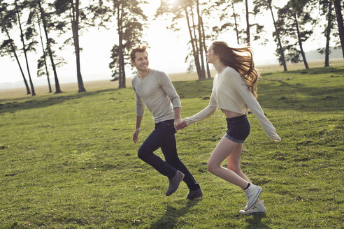 Happy young couple running hand in hand on meadow - PNEF01338