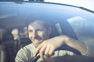 Smiling young man driving car - PNEF01341