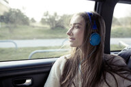 Young woman with windswept hair in a car wearing headphones - PNEF01344