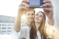 Smiling young couple taking a selfie outdoors - PNEF01347