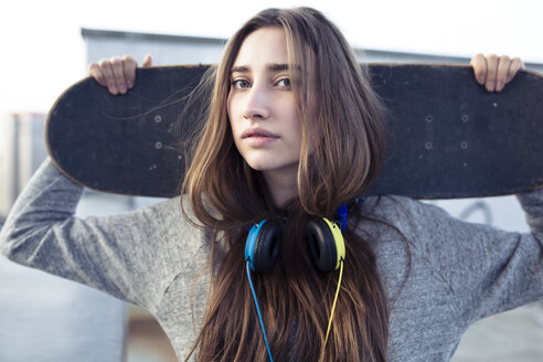 Portrait of serious young woman with skateboard and headphones - PNEF01353