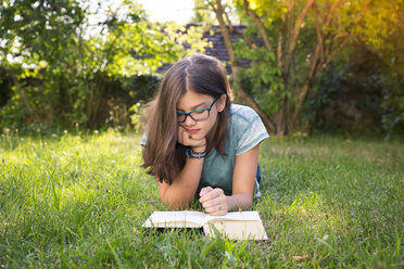 Girl lying on a meadow in garden reading book - LVF07894