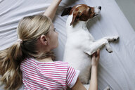 Blond girl lying on bed tickling her dog - JPF00374