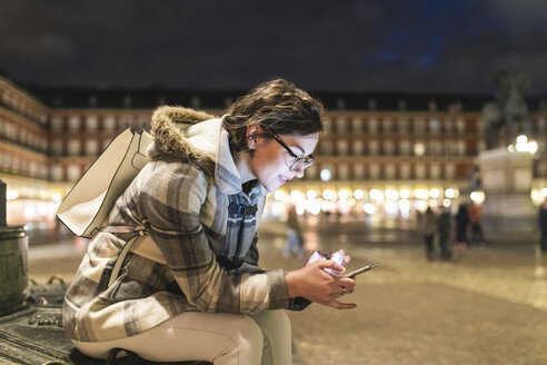 Spain, Madrid, Plaza Mayor, young woman using her smartphone - WPEF01384