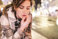 Spain, Madrid, young woman in the city at night wearing earphones - WPEF01396