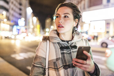Spain, Madrid, young woman in the city at night using her smartphone and wearing earphones - WPEF01399