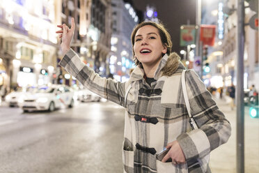 Spain, Madrid, young woman in the city at night next to Gran Via hailing a taxi - WPEF01402