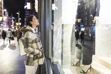 Spain, Madrid, young woman in the city at night next to Gran Via looking at a window shop - WPEF01405