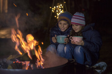 Boy and girl with mugs sitting at the fire at night - LBF02498
