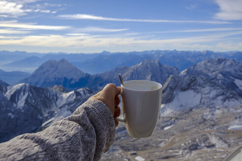 Germany, Bavaria, Zugspitze, hand holding coffee mug in mountain panorama - LBF02501