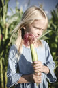 Blond girl holding corn cob in a cornfield - EYAF00034