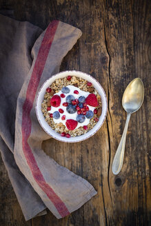 Bowl of muesli with Greek yogurt, popped quinoa, raspberries, blueberries and pomegranate seeds, from above - LVF07906