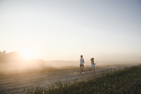 Girl and boy running on a rural dirt track - EYAF00055