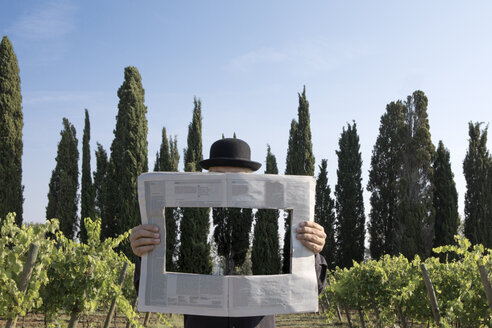 Italy, Tuscany, invisible man surrounded by cypresses reading newspaper with a hole - PSTF00330