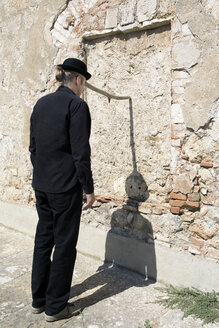 Man wearing a bowler hat balancing a stick at a stone wall - PSTF00348