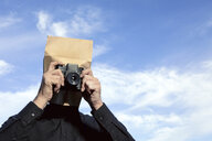Man with paper bag above his head taking a picture - PSTF00354