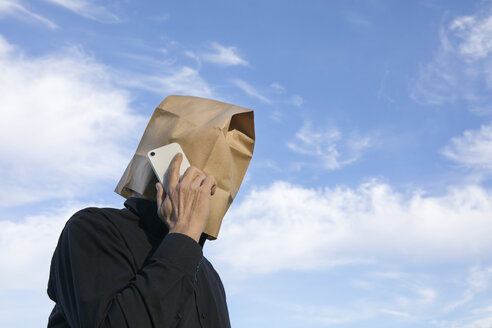 Man with paper bag above his head talking on cell phone - PSTF00360