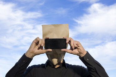 Man with paper bag above his head using cell phone - PSTF00363