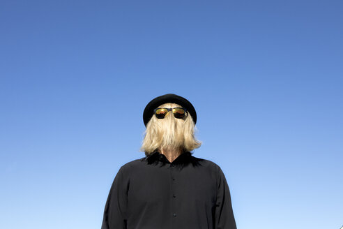 Blond hair covering man's face wearing sunglasses and bowler hat - PSTF00366