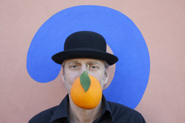 Portrait of man with an orange at a wall with question mark wearing a bowler hat - PSTF00369