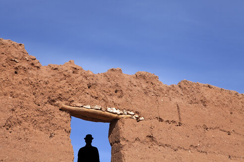 Morocco, Ait-Ben-Haddou, silhouette of man wearing a bowler hat under loam wall - PSTF00375