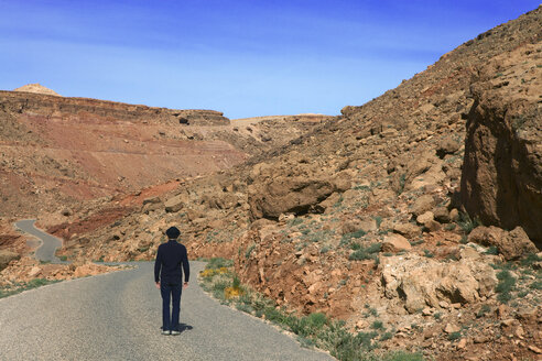 Morocco, Ounila Valley, rear view of man wearing a bowler hat standing on road in the mountains - PSTF00378
