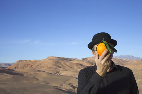 Morocco, Ounila Valley, man wearing a bowler hat holding an orange in front of his face - PSTF00381