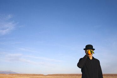 Morocco, Ounila Valley, man wearing a bowler hat holding an orange in front of his face - PSTF00384