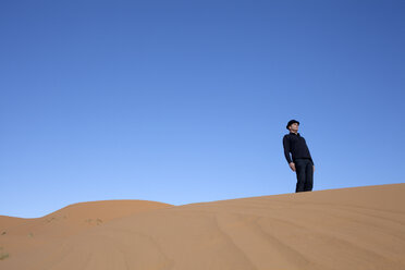 Morocco, Merzouga, Erg Chebbi, man wearing a bowler hat standing crooked on desert dune - PSTF00390
