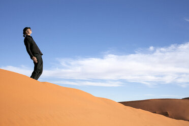 Morocco, Merzouga, Erg Chebbi, man wearing a bowler hat standing crooked on desert dune - PSTF00393