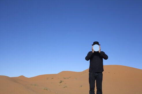Morocco, Merzouga, Erg Chebbi, man wearing a bowler hat holding mirror in front of his face in desert dune - PSTF00396