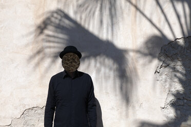 Morocco, Essaouira, man with obscured face wearing a bowler hat at a wall - PSTF00411