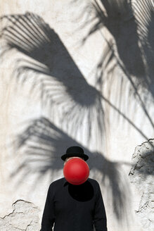 Morocco, Essaouira, man wearing a bowler hat with red balloon in front of his face at a wall - PSTF00414