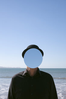 Morocco, Essaouira, man wearing a bowler hat with mirror in front of his face at the sea - PSTF00423