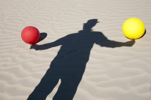Shadow of man wearing a bowler hat and two balloons in sand - PSTF00426