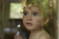 Portrait of little girl behind windowpane eating - AMEF00048