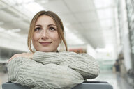 Portrait of smiling young woman at the airport sitting in waiting area - PNEF01366
