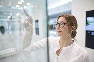 Young businesswoman touching virtual touchscreen - PNEF01375