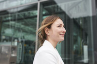 Portrait of smiling young businesswoman in front of a building - PNEF01384