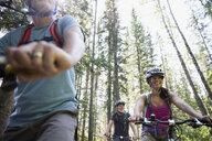 Friends mountain biking below trees in woods - HEROF31040