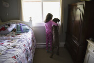 Girl and dog hugging looking out bedroom window - HEROF31046