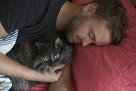 Man sleeping with cat in bed - HEROF31052