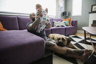 Dog laying by father baby son living room - HEROF31079